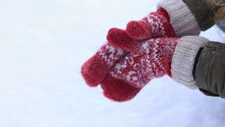 Female hands in knitted mittens making snowball