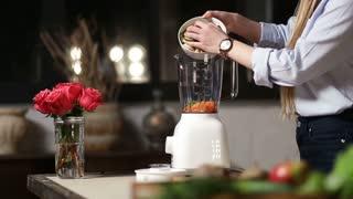 Female putting chopped food ingredients in blender
