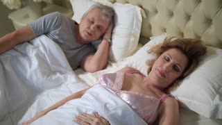 Happy mature woman waking up and smiling
