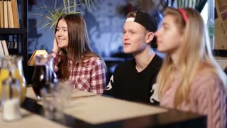 Happy teenage friends sitting and chatting in cafe