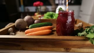 Jar of fresh beet smoothie with vegetables in tray