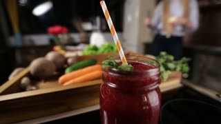 Jar of fresh beetroot smoothie with striped straw