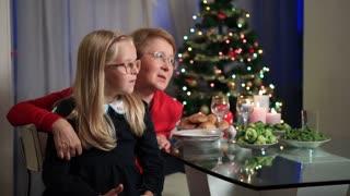 Little girl sitting on granny's lap on Christmas