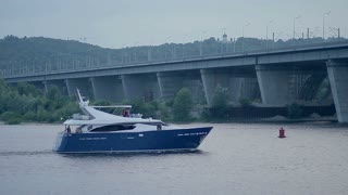 Luxury motor yacht sailing on river over cityscape