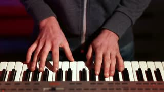 Man hands playing electronic keyboard on stage