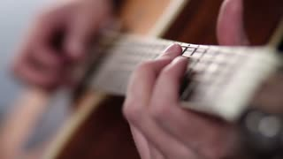 Man's fingers playing on guitar frets