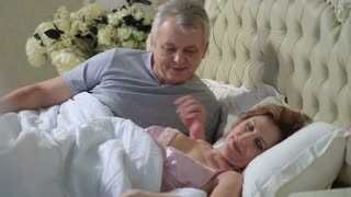 Mature loving couple lounging in bed after awaking