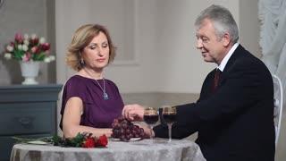 Mature woman feeding man with grapes at restaurant