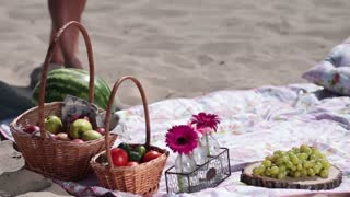Picnic basket on colorful blanket on the beach