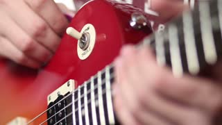Rock musician with electric guitar fretting chord