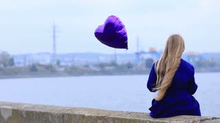 Sad girl with broken heart holding heart balloon