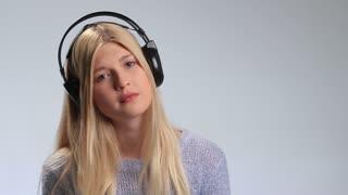 Sad girl with headphones listening to music