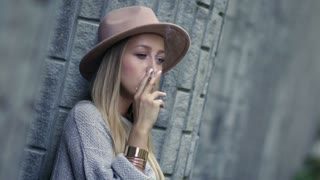 Sad lonely woman smoking cigarette and thinking