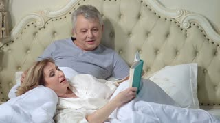 Senior couple reading a book in bed