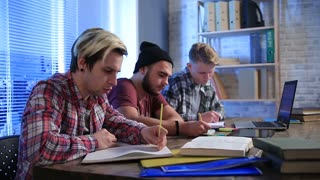 Several classmates taking lecure notes to notebook