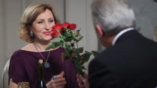 Smiling senior woman receiving flowers from man