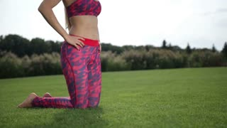 Sporty woman doing hip flexor stretch in the park