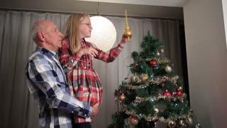 Sweet little girl adjusting Christmas tree top