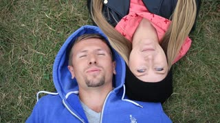 Sweethearts students lying on grass head to head