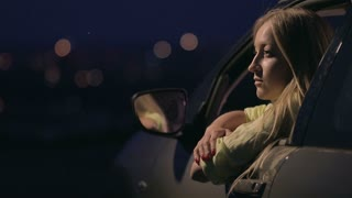 Thoughtful woman enjoying landscape of night city from open car's window on the observation deck. Dreaming young lady leaning her arms on car's window and looking at night city lights