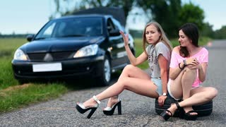 Upset women sitting on spare wheel on a road