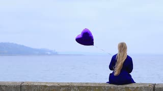 Upset young woman holding violet heart balloon