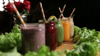 Various freshly blended smoothies on wooden tray