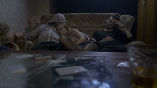 A group of three young drug addicts lying on sofa passed out after overdose at night at home. Cocaine bags, powder, money roll and cigarette butts on mirror table. Drug and alcohol abuse. Dolly shot