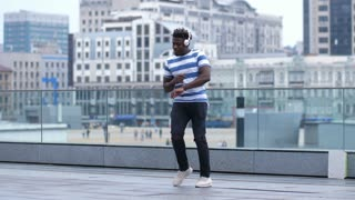 Active african american hipster in headphones dancing afrohouse style in urban setting against cityscape background. Flexible trendy black male performing afrobeat dance in city street. Slow motion.