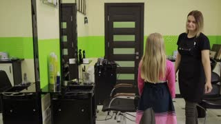 Adorable girl visiting hairstylist in barber shop