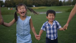 Adorable laughing asian siblings holding hands with parents and walking in summer park. Excited cute preschool girl with pigtails with her younger toddler brother enjoying a walk during family weekend