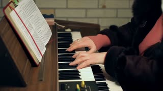 Adult woman's hands playing an old antique organ