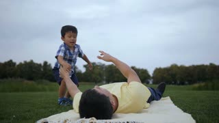 Affectionate father having fun and playing with his lovely little asian toddler boy while lying on blanket in summer park. Positive single dad lifting his laughing son up and keeping above in nature.