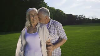 Affectionate portrait of beautiful senior couple on green lawn outdoors. Attractive senior woman and man with gray hair cuddling. Husband tenderly kissing wife's cheek and shoulder. 180 degree shot
