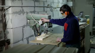 Artisan boring holes in wood with drilling machine