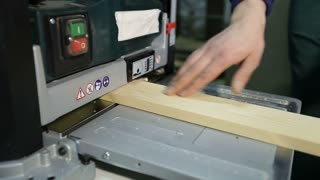 Artisan working with planing machine in workshop