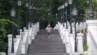 Athletic mature woman in sportswear running up beautiful stairs in city park. Back view of slim sporty female working out in the morning doing cardio. Healthy lifestyle and sport concept