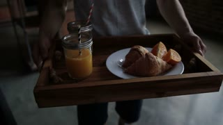 Attentive man serving breakfast to woman in bed