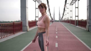 Attractive middle-aged redhed woman with slim, fit sporty body practiving karate on city bridge. Healthy female performing karate leg kicks to camera and smiling while working out in the morning