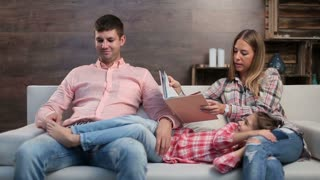 Attractive parents with child reading book at home