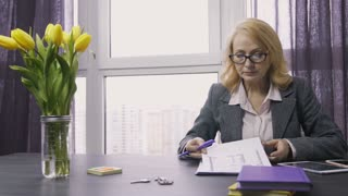 Attractive senior real-estate agent sitting at desk in office, preparing to meet clients. Serious saleswoman working on documents, reading agreement and house plan to sign sale contract. Dolly shot