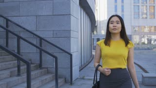 Attractive young adult asian business lady walking going to job in office center in the morning. Determined female executive in formalwear walking fast to workplace. Steadicam shot, front view