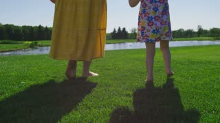 Back view close-up shot of mother and little toddler daughter's legs walking barefoot on green grass to the pond. Mom and her girl having fun in park on green meadow walking to pond. Steadicam shot