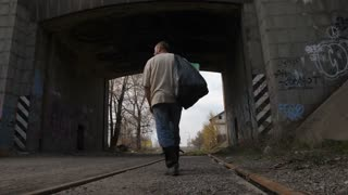 Back view full length of mature unemployed homeless man walking under bridge tunnel in city. Poor male collecting plastic to earn money with recycling. Steadicam stabilized shot.