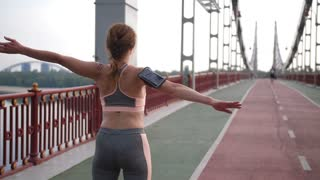 Back view medium shot of senior redhead woman in sportswear and mobile holder stretching arms and shoulders on city bridge during morning workout. Fit middle-aged female warming up before running