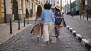 Back view of diverse multiethnic fashion women walking on city street holding shopping bags. Group of three girlfriends embracing after successful shopping day. Happy shopaholic friends with purchases