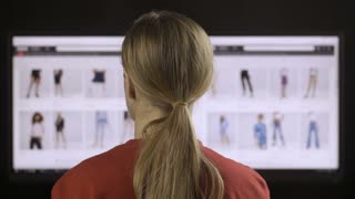 Back view of female browsing clothing online shop on wide screen computer at home. Woman in red t-shirt checking best offers and discouts and using credit card to purchase online in online store.