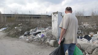 Back view of mature homeless man in dirty t-shirt and jeans walking along garbage dump in city with trash bins looking for plastic to recycle. Homelessness and pollution concept. Steadicam shot