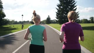 Back view of senior fitness women running on road