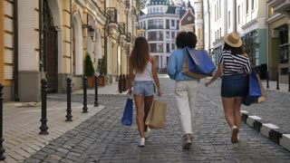 Back view of three diverse shopper females walking with shopping bags in boutique city area. Multiethnic young girls purchasing apparel in clothing stores together during shopping weekend.